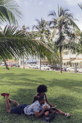 USA, Florida, Miami Beach, young couple using tablet and laptop on lawn in a park - BOYF00873