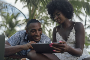 Young woman showing tablet to boyfriend in a park - BOYF00876