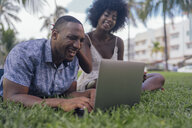 USA, Florida, Miami Beach, laughing young couple looking at laptop on lawn in a park - BOYF00879