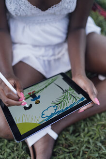 Close-up of young woman in a park drawing on graphics tablet - BOYF00882