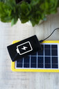 Renewable energy technology, solar panel charging a mobile phone battery - GEMF02496