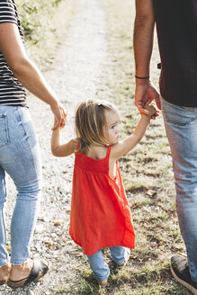 Girl walking on parent's hands on a field path - HMEF00055