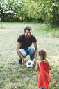 Happy father playing football with daughter on meadow - HMEF00058