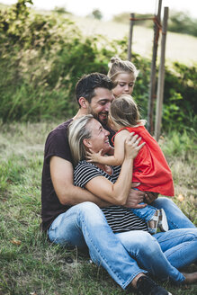 Happy family with two daughters sitting on a meadow - HMEF00064
