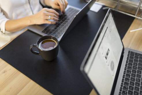 Close-up of woman using laptop at desk in office - VGF00092