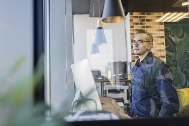 Man standing in office looking out of window - VGF00098