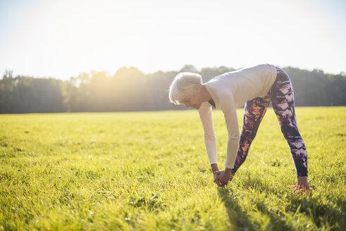 Senior woman doing gymnastics on rural meadow - DIGF05433