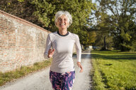 Happy senior woman running along brick wall in a park - DIGF05436
