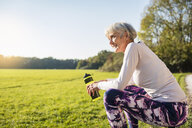 Smiling sportive senior woman holding bottle in rural landscape - DIGF05439