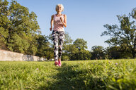 Senior woman running on rural meadow - DIGF05448