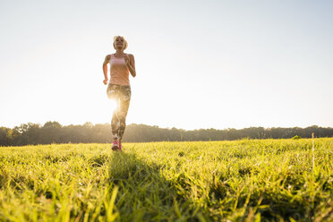 Senior woman running on rural meadow at sunset - DIGF05460