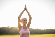 Smiling senior woman doing yoga on rural meadow at sunset - DIGF05463