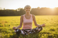 Portrait of smiling senior woman in lotus position on rural meadow at sunset - DIGF05466