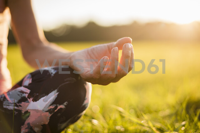 Detail of woman in lotus position on rural meadow at sunset - DIGF05469 - Daniel Ingold/Westend61