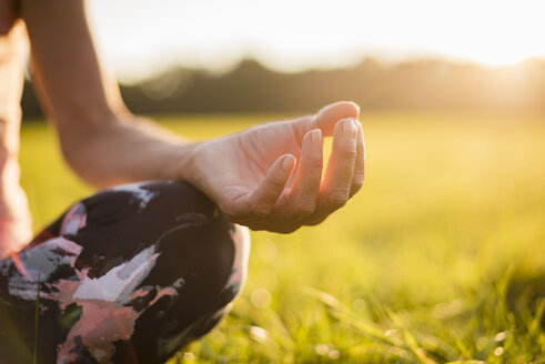 Detail of woman in lotus position on rural meadow at sunset - DIGF05469