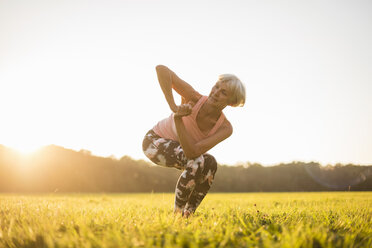 Senior woman doing yoga on rural meadow at sunset - DIGF05472