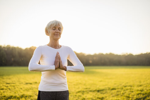 Senior woman doing yoga on rural meadow at sunset - DIGF05475