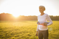 Senior woman holding yoga mat on rural meadow at sunset - DIGF05478