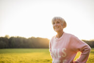 Smiling senior woman standing on rural meadow at sunset - DIGF05481