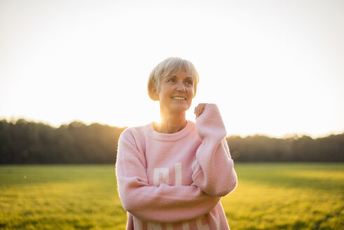 Portrait of smiling senior woman standing on rural meadow at sunset - DIGF05484