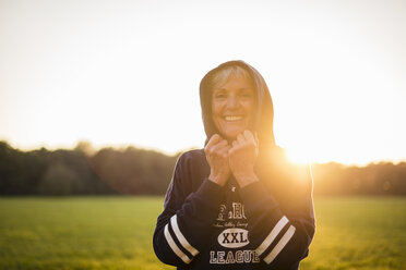 Portrait of smiling senior woman wearing a hoodie standing on rural meadow at sunset - DIGF05487