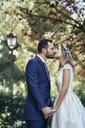 Happy bridal couple kissing in a park while holding hands - JSMF00562