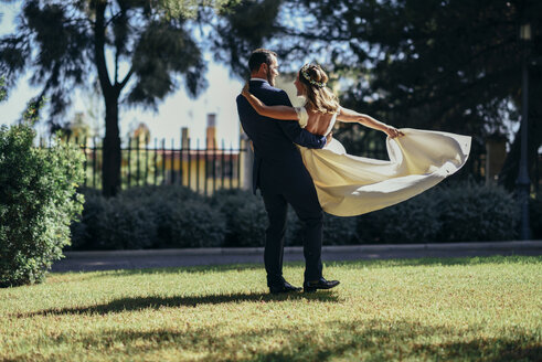 Bridal couple enjoying their wedding day in a park - JSMF00565
