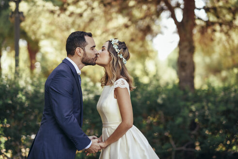 Bridal couple kissing in a park while holding hands - JSMF00568