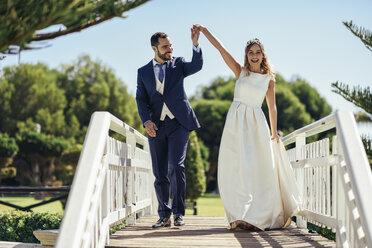 Bridal couple enjoying their wedding day in a park - JSMF00571