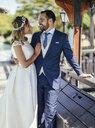 Bridal couple enjoying their wedding day in a park - JSMF00577