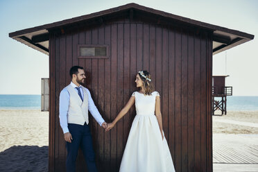 Bridal couple standing hand in hand in front of beach hut looking at each other - JSMF00580