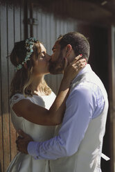 Kissing bridal couple in front of a beach hut - JSMF00583