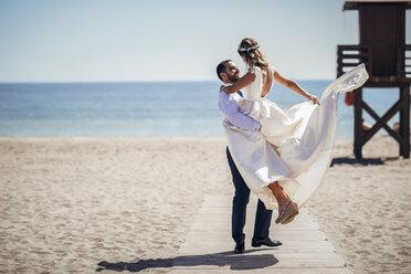 Happy bridal couple enjoying their wedding day on the beach - JSMF00586