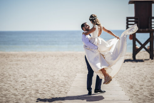 Happy bridal couple enjoying their wedding day on the beach - JSMF00586