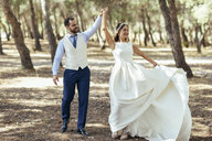 Happy bridal couple dancing together in pine forest - JSMF00589