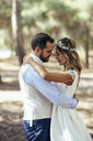 Happy bridal couple dancing together in pine forest - JSMF00592
