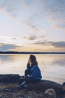 Young woman sitting at lake Inari, looking at view, Finland - RSGF00094
