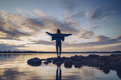 Young woman standing at lake Inari, with arms outstretched, Finland - RSGF00100