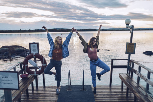 Two girl friends standing on one leg on a pier at Lake INari, Finland - RSGF00106