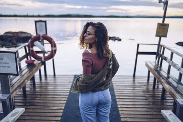 Pretty young woman posing on a pier at Lake Inari, Finland - RSGF00109