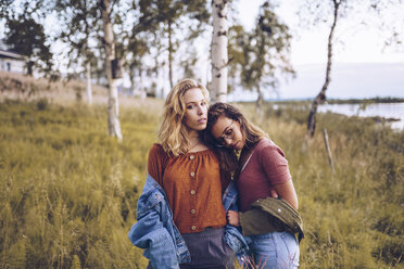 Two girl friends leaning on each other on a lakeshore - RSGF00112