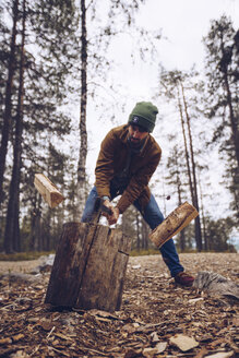Young man chopping woog in the forest - RSGF00118