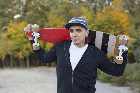 Portrait of man with skateboard on shoulders in autumn - VGF00099