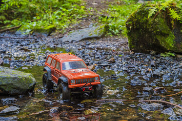 Germany, remote control car driving through brook - FRF00757