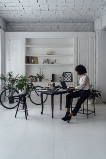 Mid adult woman working in her home office, using laptop - BOYF00891