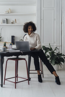 Mid adult woman working in her home office, using laptop - BOYF00894