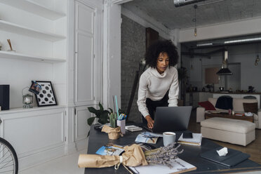 Mid adult woman working in her home office, using laptop - BOYF00903