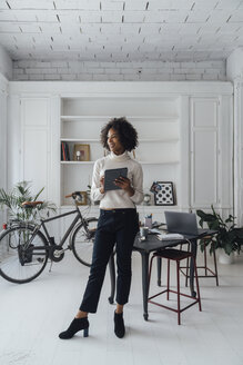 Mid adult freelancer standing in her home office, using digital tablet - BOYF00909