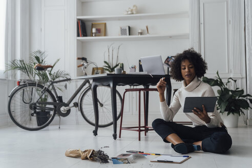 Disigner sitting on ground of her home office, using digital tablet - BOYF00912
