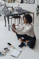 Disigner sitting on ground of her home office, using digital tablet - BOYF00915
